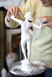 Brazos de la fijación del escultor a la figurilla sin brazo. Foto de archivo libre de regalías