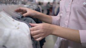 Brazos de la muchacha de los clientes que consideran la nueva ropa de moda en suspensiones en tienda durante los descuentos de la almacen de metraje de vídeo