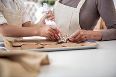 Brazos de la muchacha que exprimen el líquido dulce en los pasteles de la Navidad Foto de archivo libre de regalías
