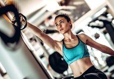 Brazos del entrenamiento de la mujer con las correas de la aptitud del trx en el gimnasio imagen de archivo libre de regalías