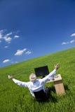 Brazos del hombre de negocios levantados en el escritorio en campo verde Fotografía de archivo