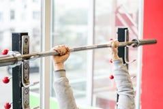 Brazos del hombre que se resuelven en el gimnasio, atleta del principiante que hace ejercicio de la prensa de banco foto de archivo