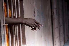 Brazos del preso que se reclinan sobre barras de la célula Imagen de archivo