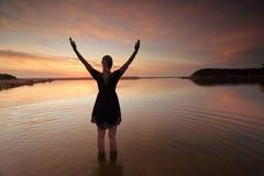 Brazos extendidos de la mujer que elogian éxito del día perfecto Foto de archivo
