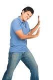 Brazos extendidos masculinos que empujan contra objeto lateral Foto de archivo libre de regalías