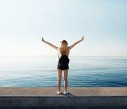 Brazos felices y libremente abiertos de la mujer de la libertad en la playa en la salida del sol soleada imagen de archivo libre de regalías