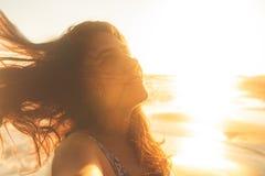 Brazos felices y libremente abiertos de la mujer de la libertad en la playa en la puesta del sol soleada imagen de archivo
