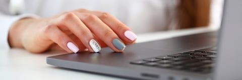 Brazos femeninos en mecanografiar usando la PC del ordenador portátil en la oficina imagen de archivo libre de regalías