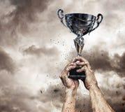 Brazos masculinos cosechados con la taza del ganador fotos de archivo
