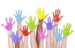 Brazos multiétnicos aumentados y manos pintadas coloridas Fotos de archivo libres de regalías