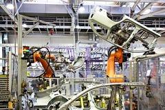 Brazos robóticos en una fábrica del coche Imagenes de archivo