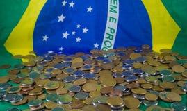 Brazylijczyk monety na tło fladze Brazylia, Pieniężna rzeczywistość fotografia stock
