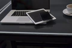 bärbar datordator, digital minnestavla och mobiltelefon på den svarta tabellen Arkivfoto