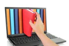 Bärbar datordator med kulöra böcker Arkivfoton