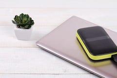 Bärbara datorn och bärbart yttre hårddiskdrev med USB kablar på vit träbakgrund Royaltyfri Fotografi