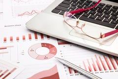 Bärbara datorn och exponeringsglas med röda affärsdiagram, grafer, forskar Arkivfoto