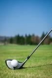 Ébrèchement d'une boule de golf sur le vert avec le club de golf de conducteur Vert Images stock