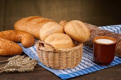 Brödprodukter med mjölkar koppen på bordduken Arkivfoto