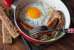 Breackfast with fried eggs. Sausages and bread royalty free stock image