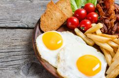 Breackfast: patate fritte, bacon ed uova fritte Fotografia Stock Libera da Diritti