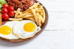 Breackfast: patate fritte, bacon ed uova fritte Fotografie Stock