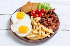 Breackfast: patate fritte, bacon ed uova fritte Immagini Stock Libere da Diritti