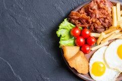 Breackfast: patate fritte, bacon ed uova fritte Immagine Stock