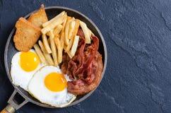 Breackfast: patate fritte, bacon ed uova fritte Fotografie Stock Libere da Diritti