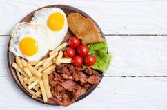 Breackfast: patate fritte, bacon ed uova fritte Immagini Stock