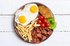 Breackfast: patate fritte, bacon, uova fritte Fotografia Stock