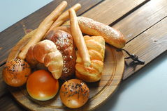 Bread. Assorted baked bread on wood plate Royalty Free Stock Photos