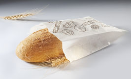 Bread. In white paper bag and piece of wheat stock photos