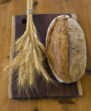 Bread. Loaf of sour dough bread with bundle of wheat Stock Images