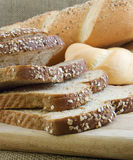 Bread. Sliced wheat bread with various breads in back Royalty Free Stock Photos