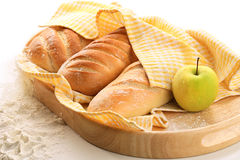 Bread and apple. Under yellow towel on the wooden tray royalty free stock images