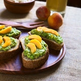 Bread with Avocado and Peach Slices Stock Images