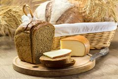 Bread and cheese sliced for sandwiches amid the loaves in a wicker basket with ears of wheat. Bread for the background in brown colors stock images