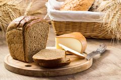 Bread and cheese sliced for sandwiches amid the loaves in a wicker basket with ears of wheat. Bread for the background in brown colors stock photos