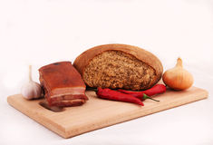 Bread, bacon, chili pepper, garlic, onion. Bacon, rye bread, garlic, chili pepper, onion on wooden cutting board on white background Stock Images