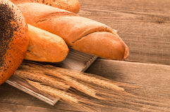 Bread, baguette, loaf and buns on the wooden desk. Horizontal Royalty Free Stock Photography