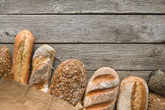 Bread bakery background. Brown and white wheat grain loaves composition on rustic wood Royalty Free Stock Image