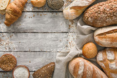 Bread bakery background. Brown and white wheat grain loaves composition on rustic wood Stock Photos