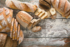 Bread bakery background. Brown and white wheat grain loaves composition on rustic wood Royalty Free Stock Photo