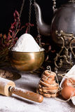 Bread baking ingredients - flour, eggs, baking powder. Baked flour-based food with antique teapot. Stock Images