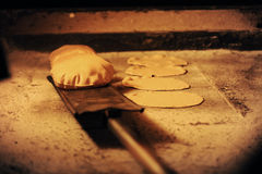 Bread baking in an open firewood oven traditional Royalty Free Stock Photo