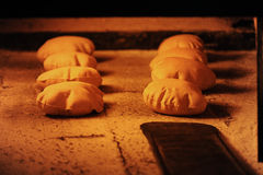 Bread baking in an open firewood oven traditional Royalty Free Stock Images