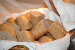 Bread Basket. Basket of sliced wheat dinner rolls that are baguette style. Cloth napkins. Focus on bread Royalty Free Stock Photo