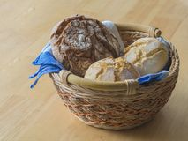 Bread basket with fresh bread and bagels with blue napkin on woo Stock Photos