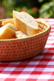 Bread in basket outdoors. Photograph of a basket of bread on an outdoor table Royalty Free Stock Images