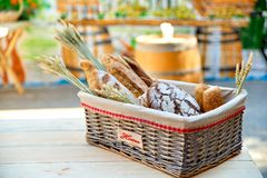 Bread basket outdoors on a wooden table in a street cafe, closeu Stock Photography